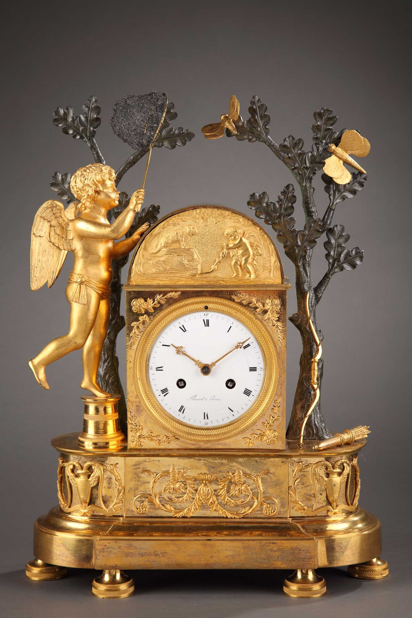 Pendule en bronze ciselé, doré et patiné. Cupidon en équilibre, essaie d'attraper dans son filet un papillon, symbole de l'amour fragile. Son carquois et arc sont posés contre le tronc.