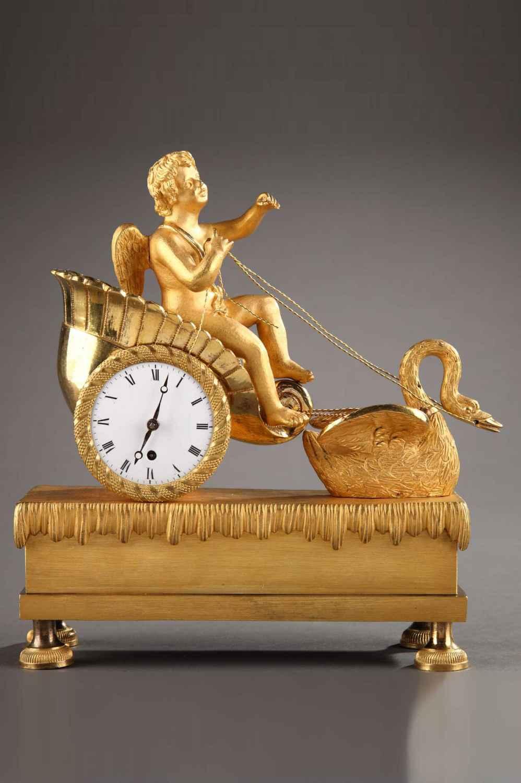 Petite pendule en bronze doré et ciselé, représentant un Amour sur un char en forme de coquillage et tiré par un cygne, sur un socle imitant l'eau.
