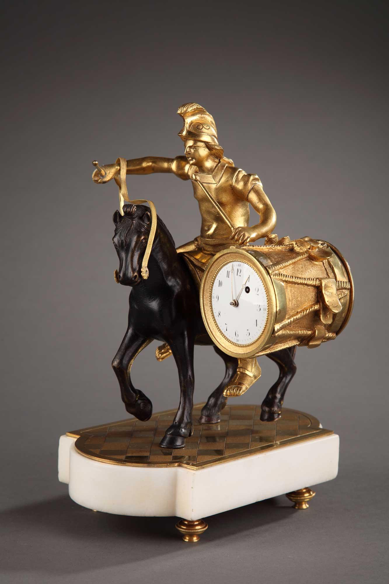 Pendulette d'époque Louis XVI en bronze doré ciselé et patiné. Mouvement de montre à coq. Base en marbre blanc sur 4 patins.