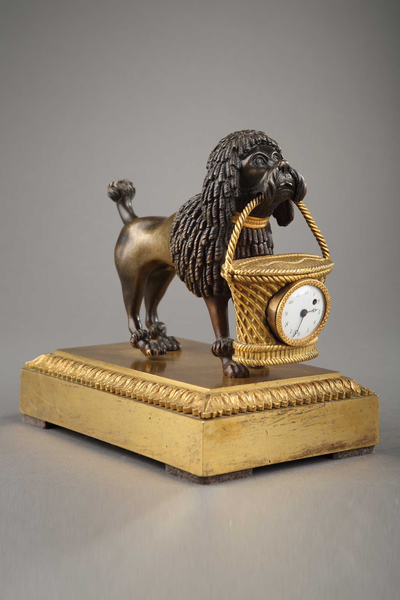 Adorable et rarissime pendulette d'époque Empire en bronze doré et patiné. Représentant un caniche tenant dans sa gueule un panier, dans lequel s'inscrit le cadran.