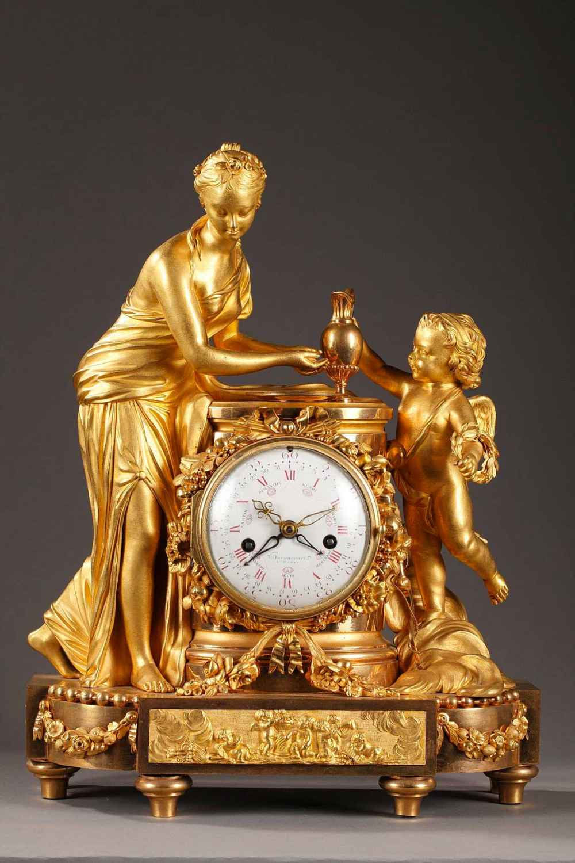 Pendule en bronze doré et ciselé d'époque Louis XVI. Vénus penchée, les mains au dessus d'une vasque attend que Cupidon, dans les nuées, lui verse de l'eau à l'aide d'une aiguière, groupe sculpté de Falconnet.
