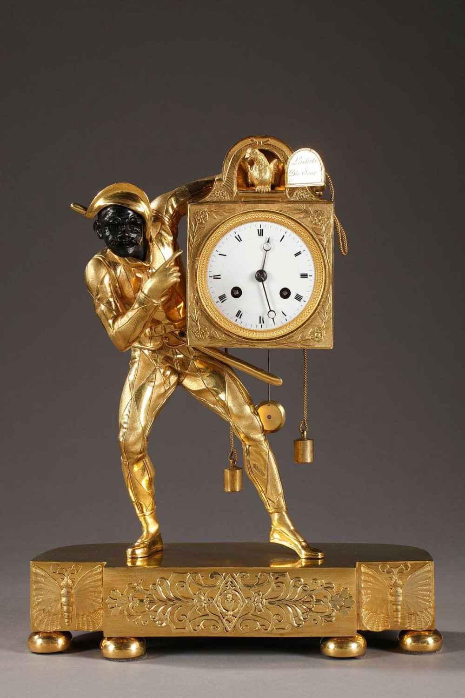 Pendule en bronze doré, ciselé et patiné d'époque Empire Le personnage, visage masqué, est représenté debout en costume à carreaux.