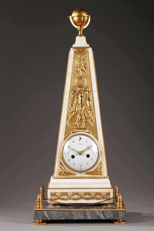 Pendule en marbre blanc et gris saint anne, bronze doré et ciselé, d'époque Louis XVI. Représente un obélisque, réduction de monuments élevés sur les places publiques pour commémorer quelques victoires ou évènements glorieux.
