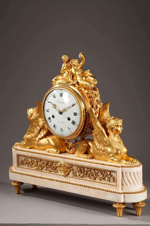 Rare pendule d'époque Louis XVI en marbre blanc et bronze doré et ciselé. Deux sphinges soutiennent le mouvement et à l'amortissement un faune et une faunesse.