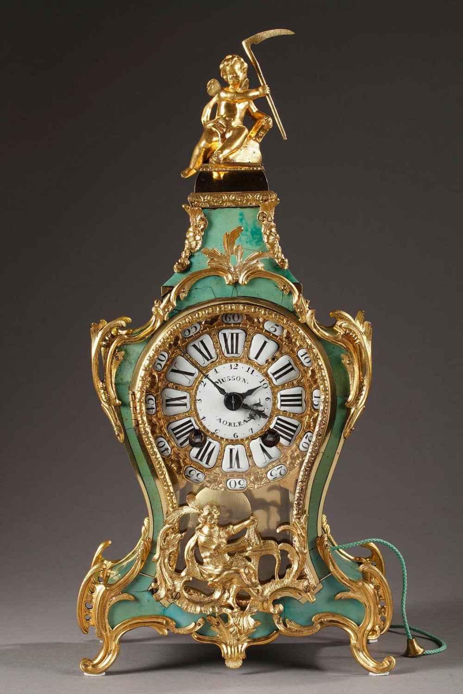 Cartel en corne verte d'époque Louis XV à garniture en bronze doré et ciselé. Cadran en bronze doré à 25 cartouches en émail blanc.