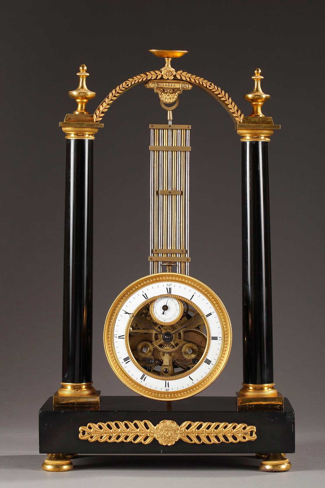Pendule portique oscillante en marbre noir, bronze doré et ciselé. Suspension au couteau, mouvement dans la lentille du balancier avec cadran annulaire pour les heures et cadran secondaire pour les secondes.