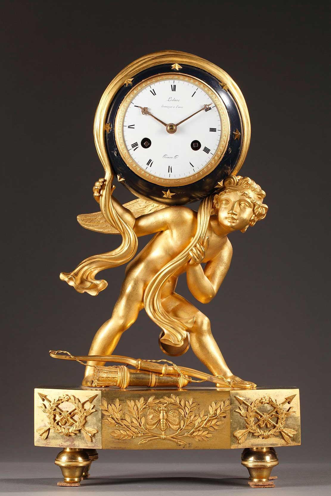 Pendule en bronze doré, ciselé et patine bleue d'époque Empire. Cupidon, dont le carquois et l'arc sont à ses pieds, maintient la voute céleste sur son épaule.