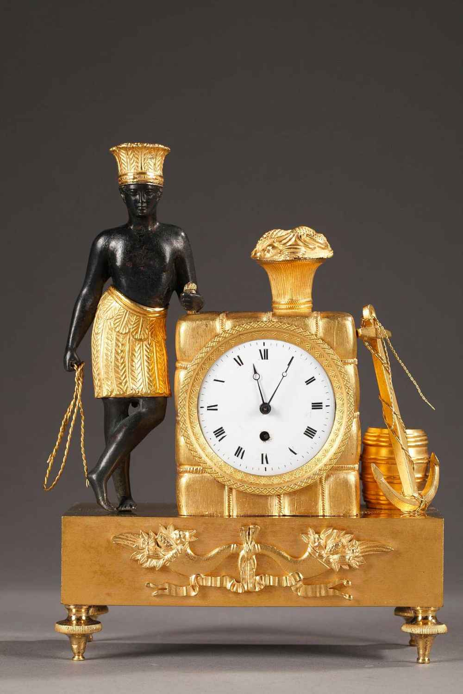 Pendulette en bronze doré, ciselé et patiné. Un africain vêtu d'un pagne et d'une coiffe à plume, est accoudé au ballot dans lequel s'inscrit le mouvement de montre à coq.