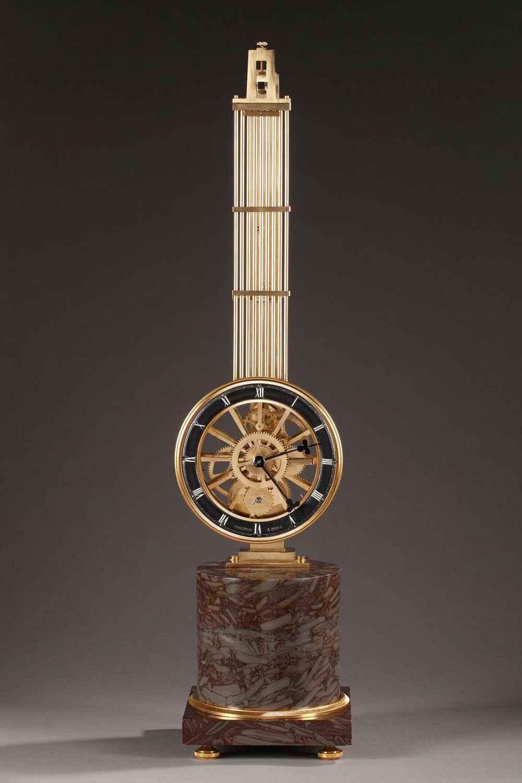 Pendule en bronze doré et ciselé. Suspension à couteau, mouvement dans la lentille du balancier avec cadran annulaire pour les heures . Cadran annulaire signéHuguenin à Paris.