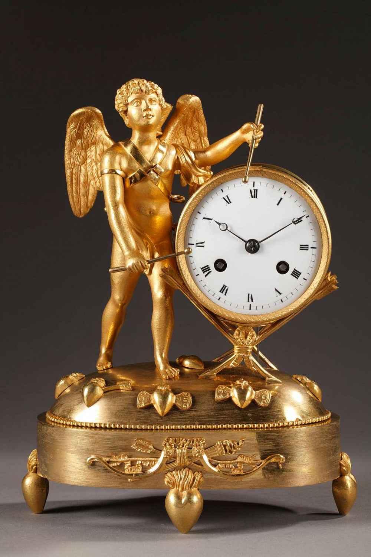 Pendule d'époque Empire en bronze ciselé et doré, présente un amour jouant du tambour.