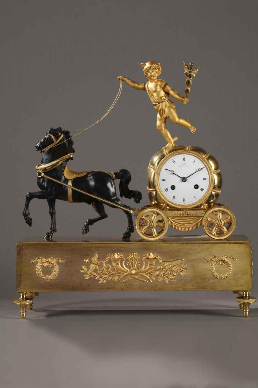 Rare pendule au char de Mercure. Mercure debout sur un ballot tient dans sa main gauche un caducée et sa main droite les rennes de son cheval patiné.